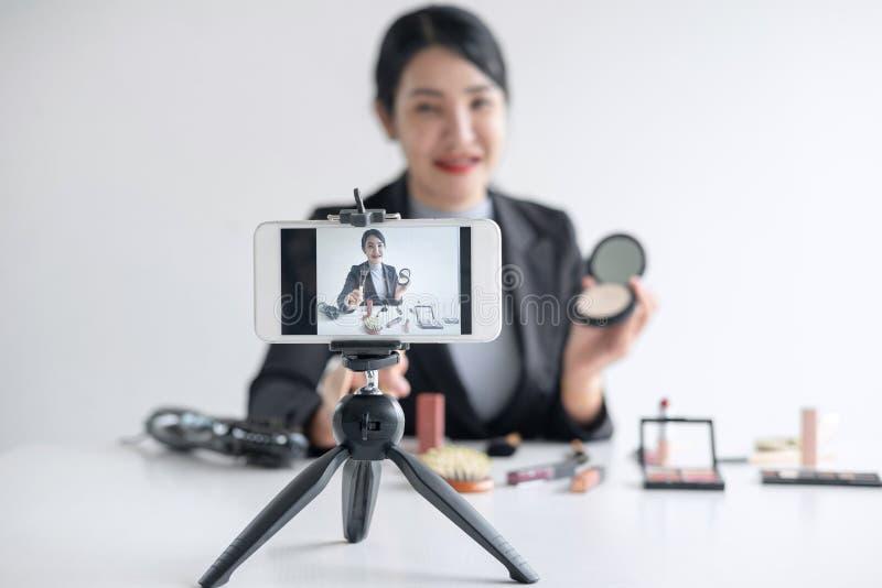 O negócio em linha em meios sociais, blogger bonito da mulher está mostrando que o produto cosmético e a transmissão da beleza tu imagem de stock royalty free