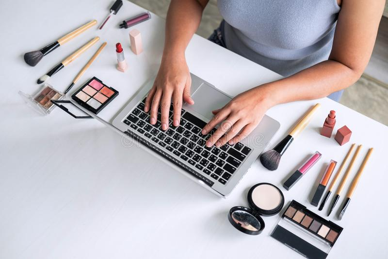 O negócio em linha em meios sociais, mulher bonita está olhando o curso em linha do blogger no portátil, mostrando a beleza tutor fotos de stock
