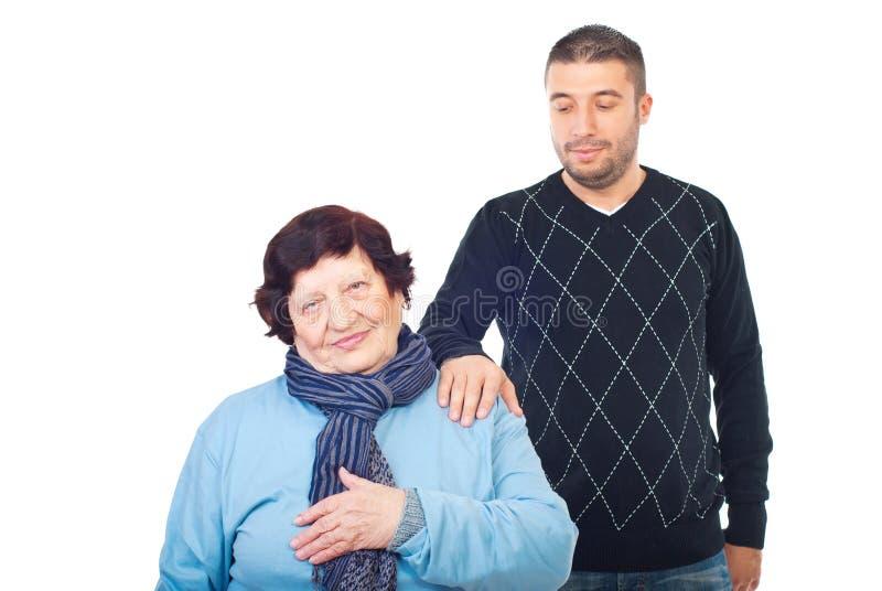 O neto consola sua avó imagem de stock