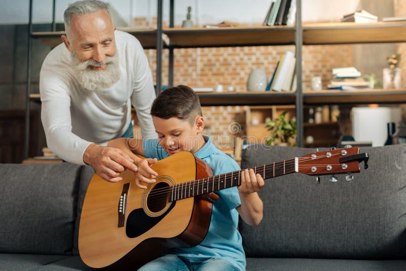 O neto de doação de primeira geração feliz derruba em jogar a guitarra fotos de stock