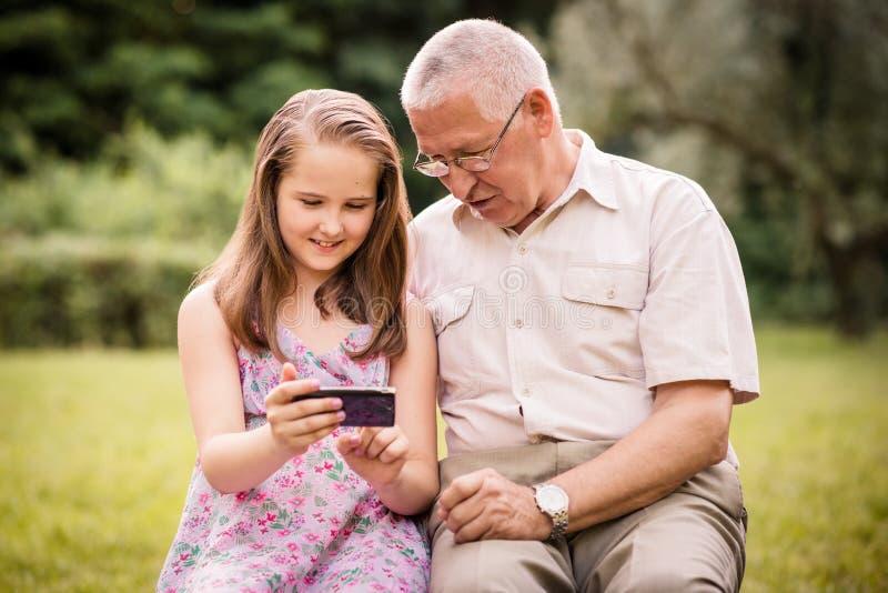 O neto mostra o smartphone de primeira geração fotografia de stock