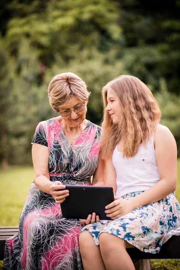 O neto mostra a tabuleta da avó foto de stock royalty free