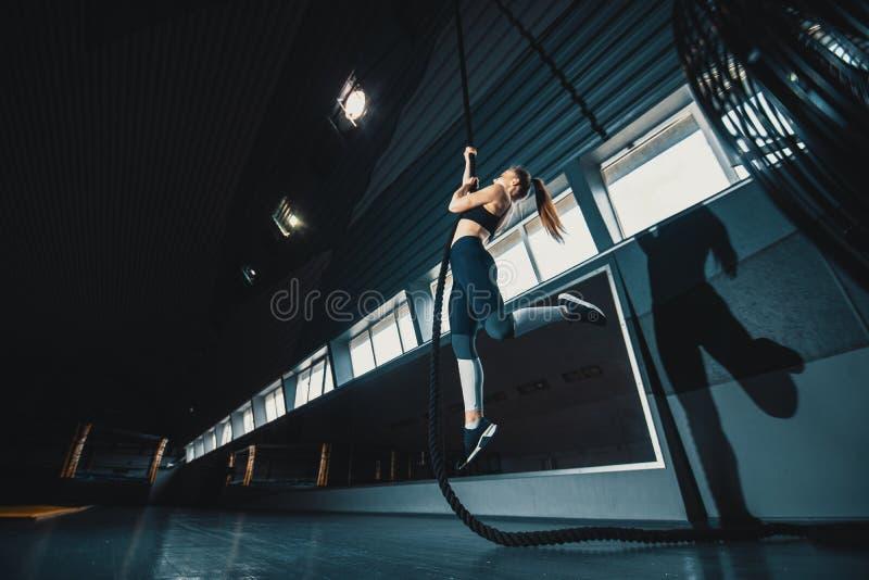O ?ngulo largo do comprimento completo disparou de uma mulher que executa escaladas da corda no gym fotografia de stock royalty free