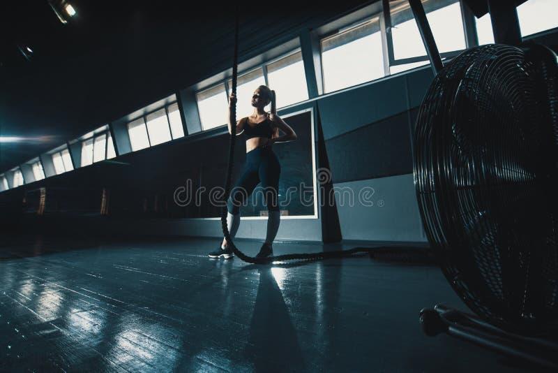 O ?ngulo largo do comprimento completo disparou de uma mulher que executa escaladas da corda no gym foto de stock