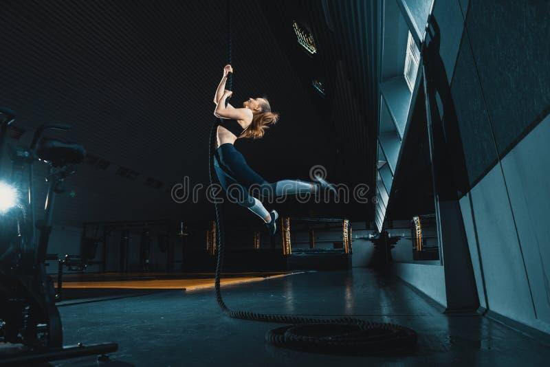 O ?ngulo largo do comprimento completo disparou de uma mulher que executa escaladas da corda no gym fotografia de stock