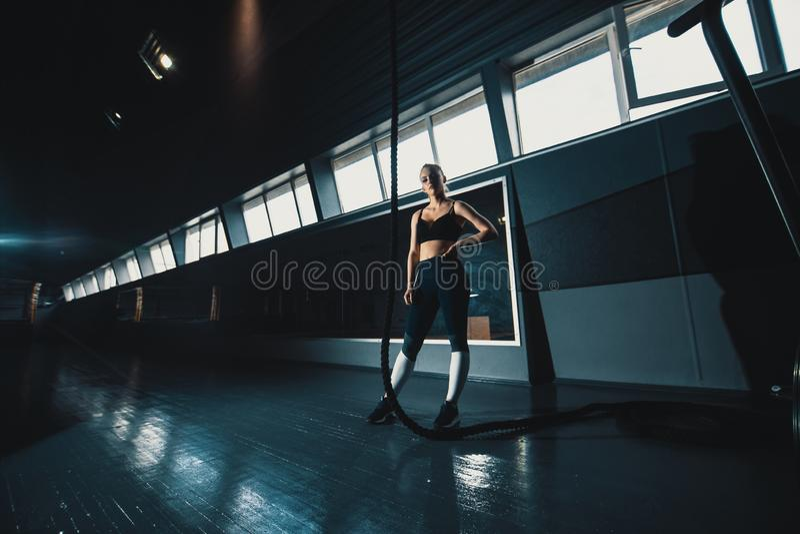 O ?ngulo largo do comprimento completo disparou de uma mulher que executa escaladas da corda no gym imagens de stock royalty free