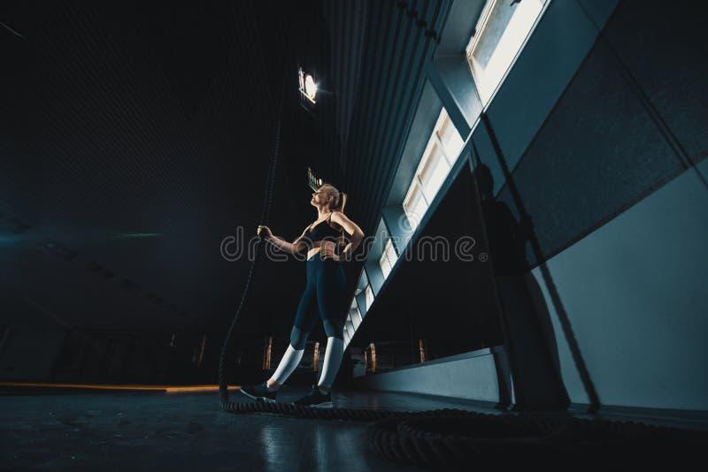 O ?ngulo largo do comprimento completo disparou de uma mulher que executa escaladas da corda no gym imagem de stock royalty free