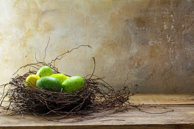 O ninho da Páscoa com verde coloriu ovos em agains de madeira rústicos das pranchas fotografia de stock