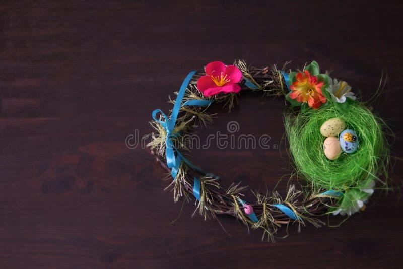 O ninho e os ovos da Páscoa envolvem-se no fundo de madeira fotos de stock