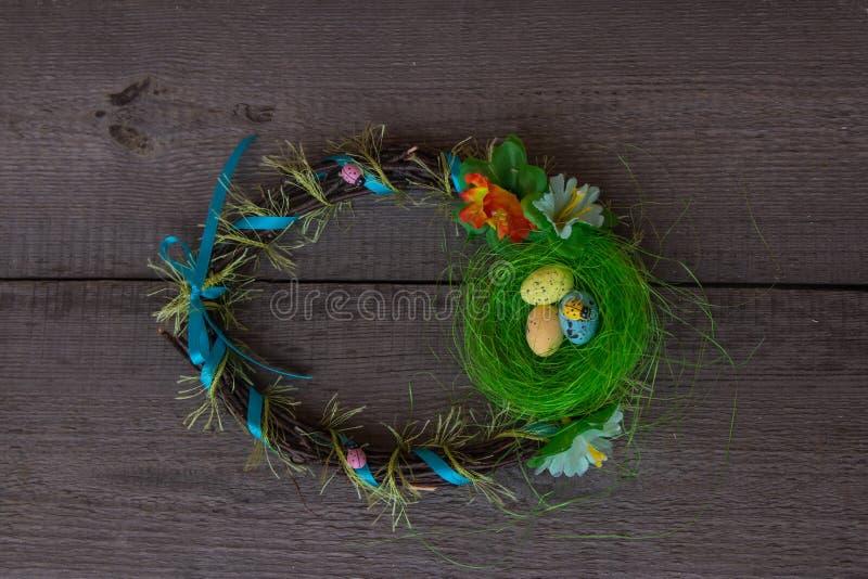 O ninho e os ovos da Páscoa envolvem-se no fundo de madeira fotos de stock royalty free