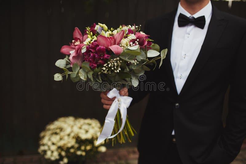 O noivo à moda está guardando o ramalhete nupcial Ramalhete do casamento nas mãos do homem foto de stock