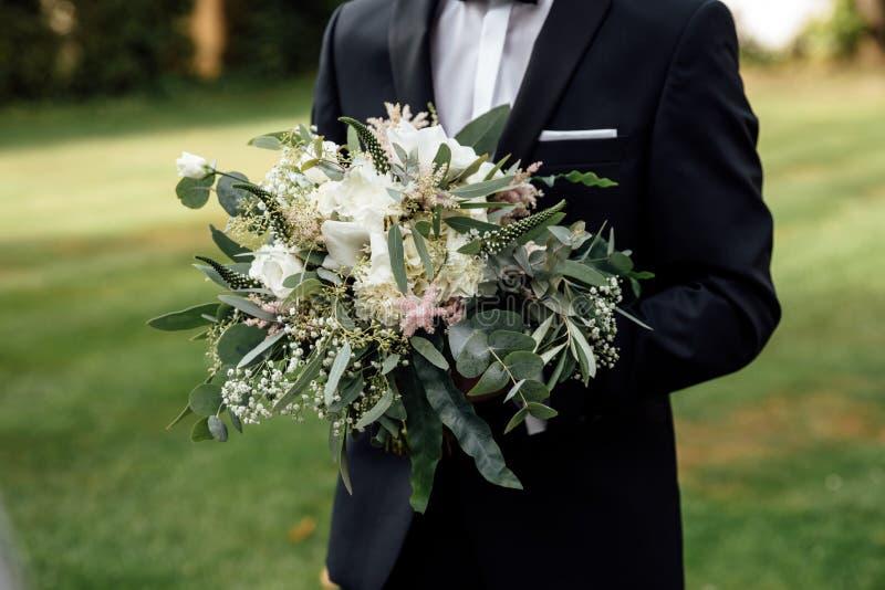 O noivo à moda está guardando o ramalhete nupcial Ramalhete do casamento nas mãos do homem fotografia de stock royalty free
