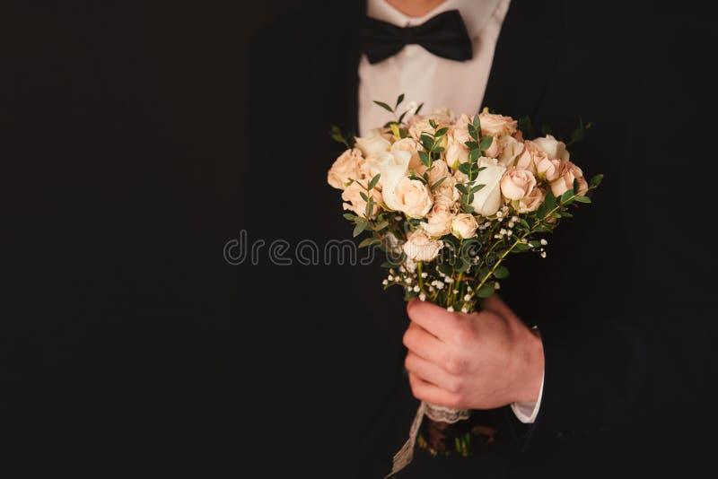 O noivo à moda está guardando o ramalhete nupcial Ramalhete do casamento nas mãos do homem fotos de stock