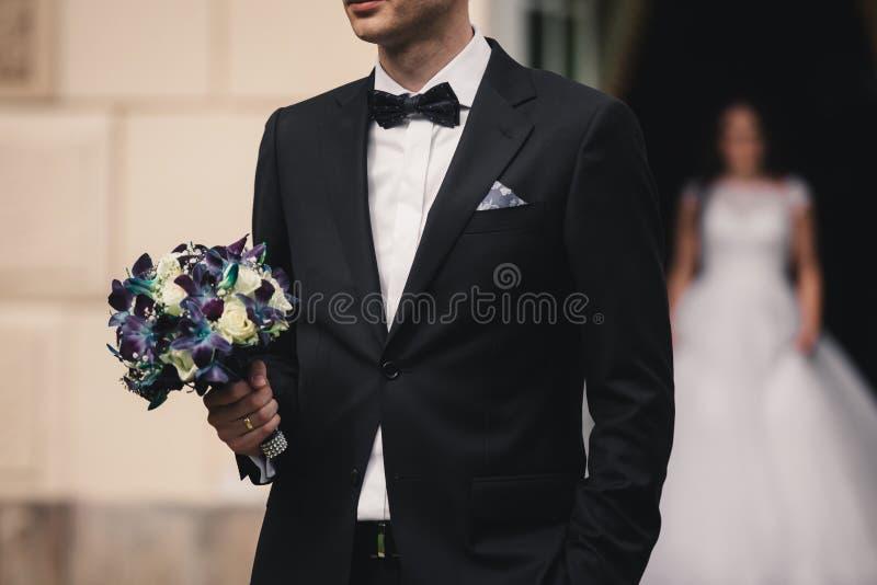 O noivo à moda está guardando o ramalhete nupcial Ramalhete do casamento nas mãos do homem imagem de stock