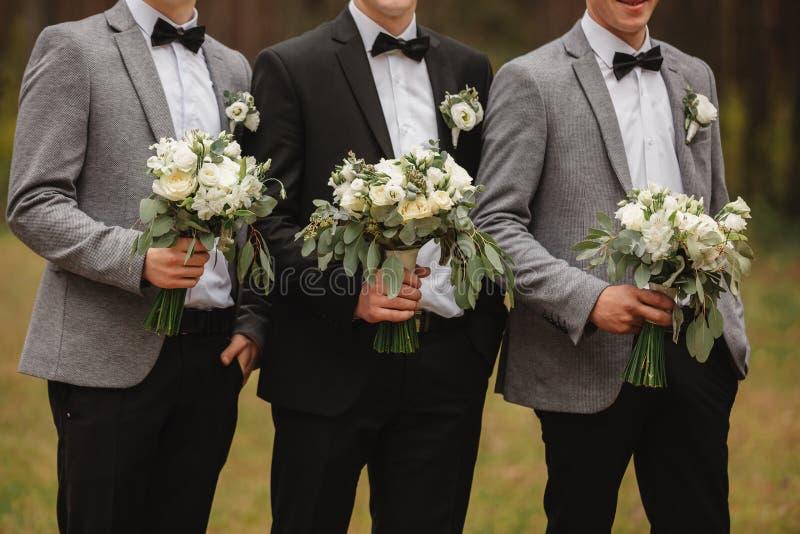 O noivo à moda está guardando o ramalhete nupcial Ramalhete do casamento nas mãos do homem fotografia de stock