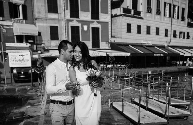 O noivo abraça delicadamente a noiva perto do mar imagens de stock