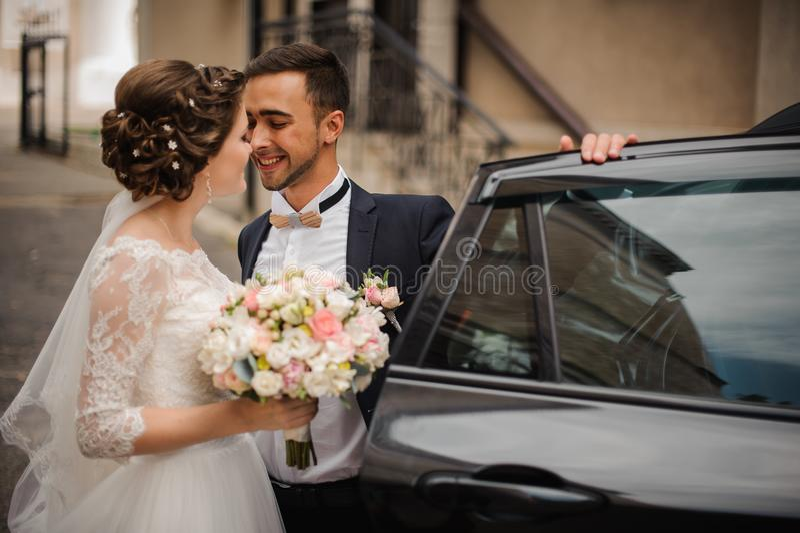 O noivo abre a porta do carro do casamento, pretendendo beijar a noiva imagem de stock royalty free