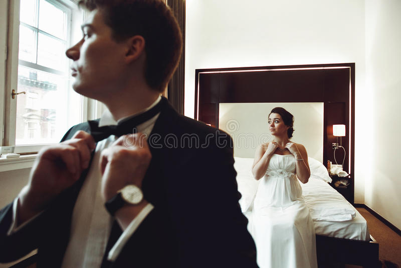 O noivo ajusta um laço quando a noiva ajustar uma colar imagem de stock royalty free