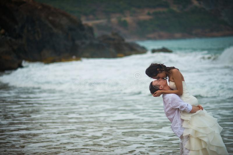 O noivo aumentou a noiva em seus braços e beijos no fundo de rochas do mar pares no amor em uma praia abandonada pelo mar foto de stock royalty free