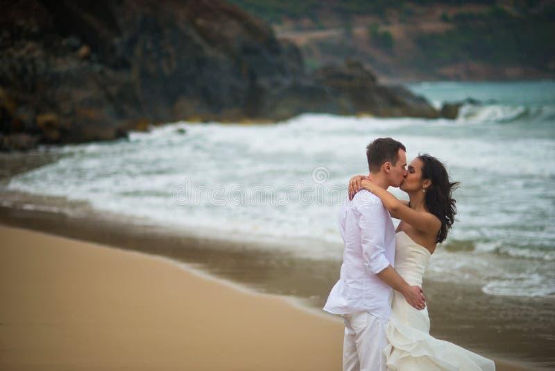 O noivo beija a noiva contra as rochas do mar pares no amor em uma praia abandonada foto de stock