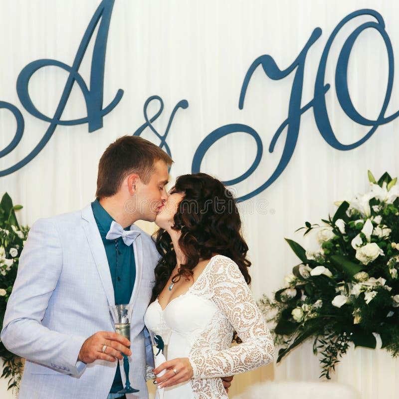 O noivo beija uma noiva que guarda o champanhe fotos de stock