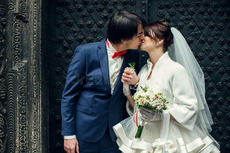 O noivo beija uma noiva que guarda seu braço atrás de seu coração imagens de stock royalty free