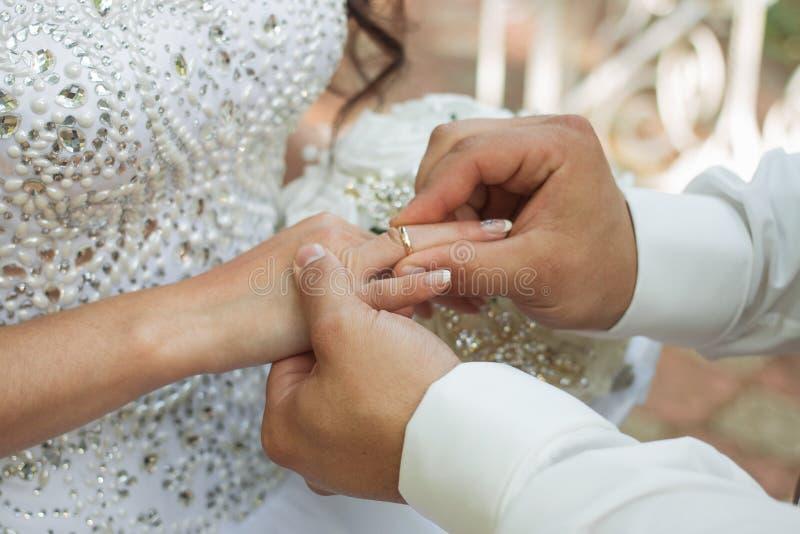 O noivo coloca o anel no bride& x27; mão de s Close up da foto imagem de stock royalty free