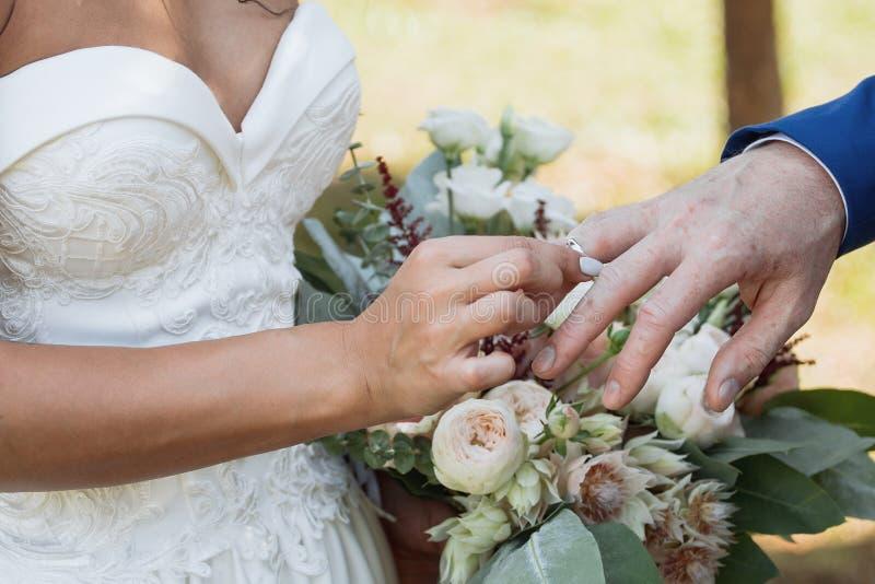 O noivo coloca o anel no bride& x27; mão de s Close up da foto fotografia de stock royalty free