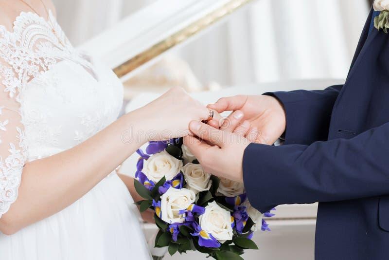 O noivo coloca o anel no bride& x27; mão de s Close up da foto fotos de stock royalty free