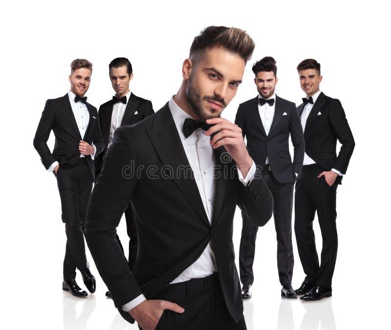 O noivo considerável com barba está na frente do pensamento do grupo imagens de stock