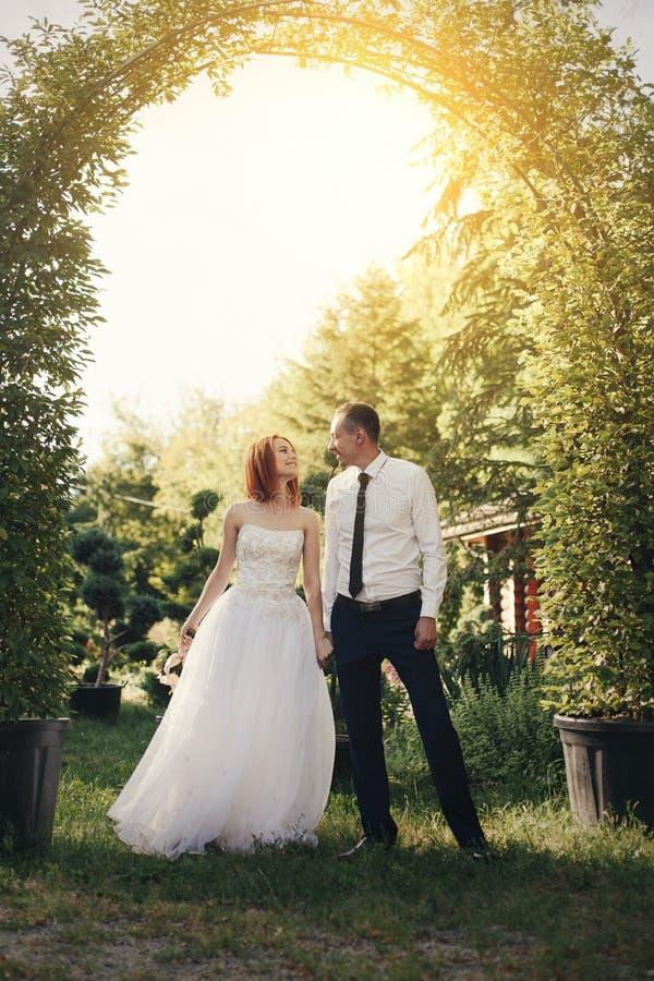 O noivo considerável guarda o bride& x27; mão de s perto da arcada verde da flor imagens de stock