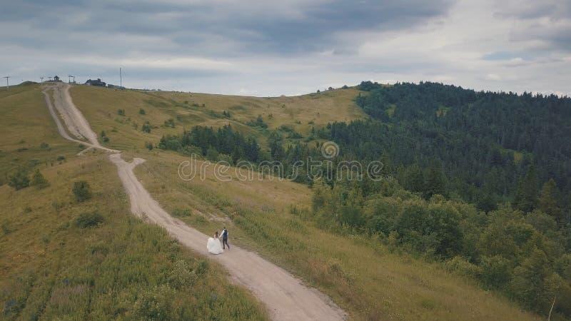 O noivo corre com a noiva em montes de uma montanha Tiro a?reo do zang?o imagem de stock royalty free