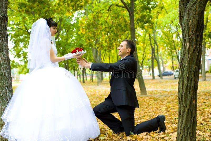 O noivo dá às flores da noiva foto de stock