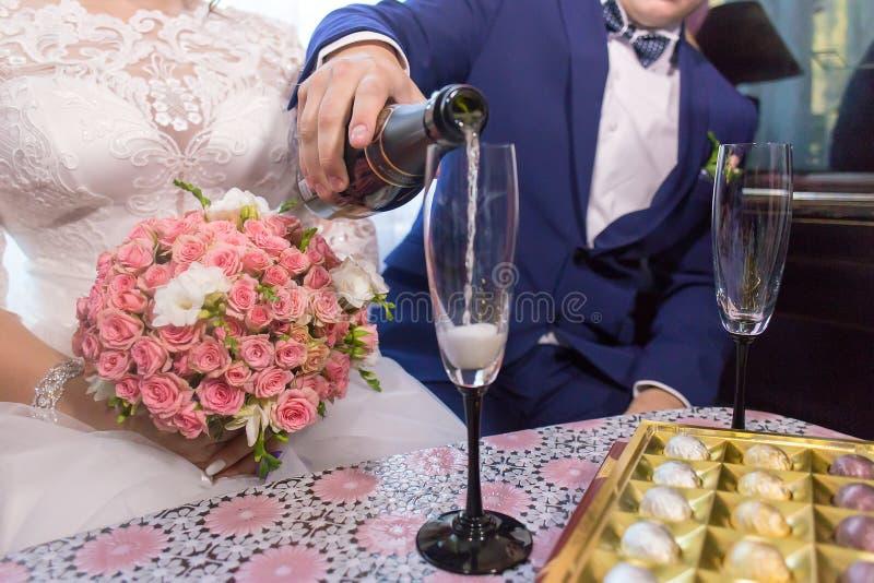 O noivo derrama o champanhe em vidros imagens de stock