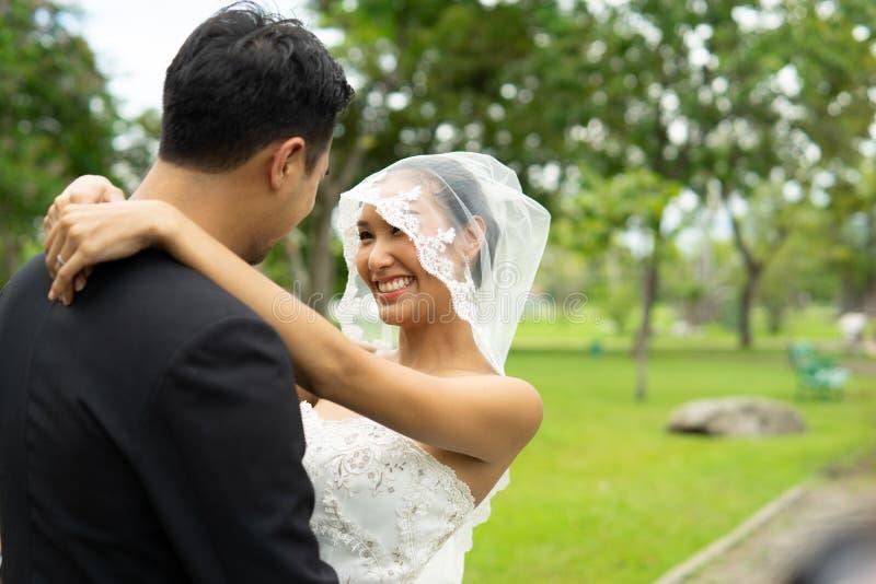 O noivo e a noiva abraçam-se com o amor e a sensação muito felizes, união dos pares imagens de stock