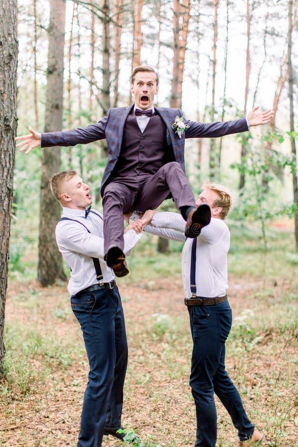 O noivo e os noivos se divertindo no Groom da floresta estão pulando com uma cara engraçada imagem de stock