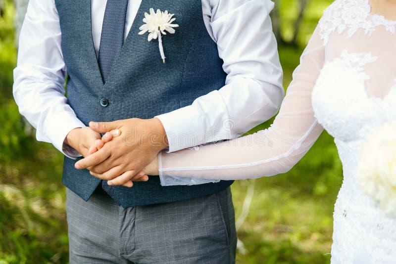 O noivo elegante guarda a mão do ` s da noiva foto de stock royalty free