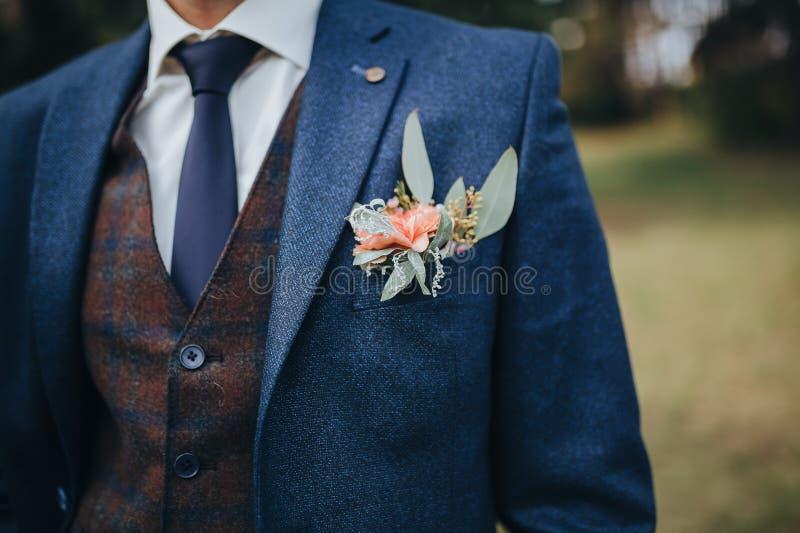 O noivo em um terno e em uma veste está nas madeiras, em uma casa de botão das flores e no eucalipto no revestimento do ` s do no foto de stock