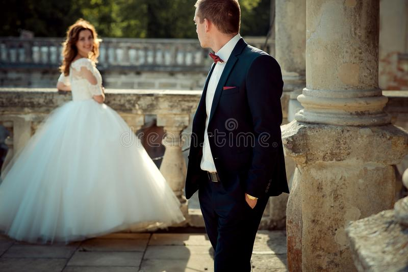 O noivo está examinando sobre seu ombro em sua noiva de sorriso de encantamento do cabelo do gengibre que está o fundo no fotos de stock