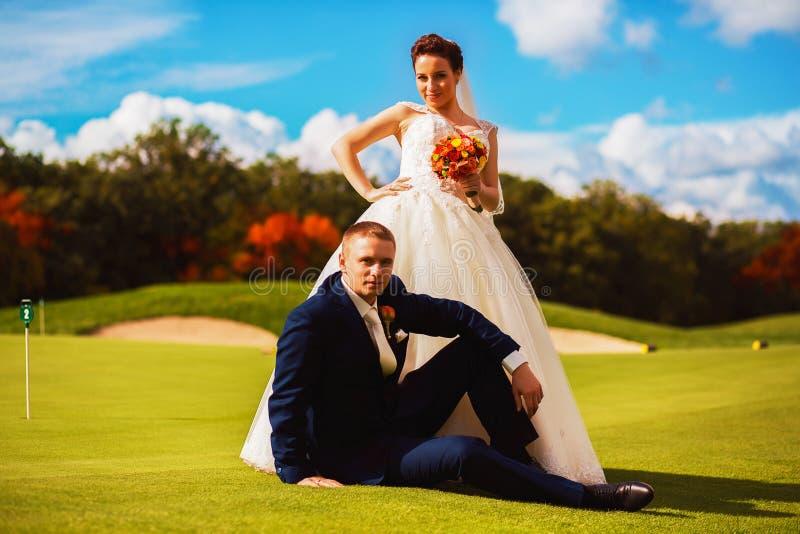 O noivo feliz e a noiva que sentam-se no golfe colocam fotos de stock royalty free