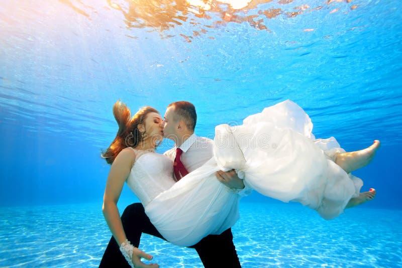 O noivo feliz mantém a noiva em seus braços subaquática na associação e beija-a no fundo da luz solar Retrato foto de stock