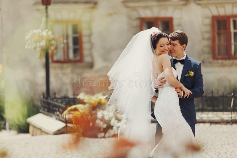 O noivo guarda a cintura da noiva que está maciamente no meio de velho imagens de stock royalty free