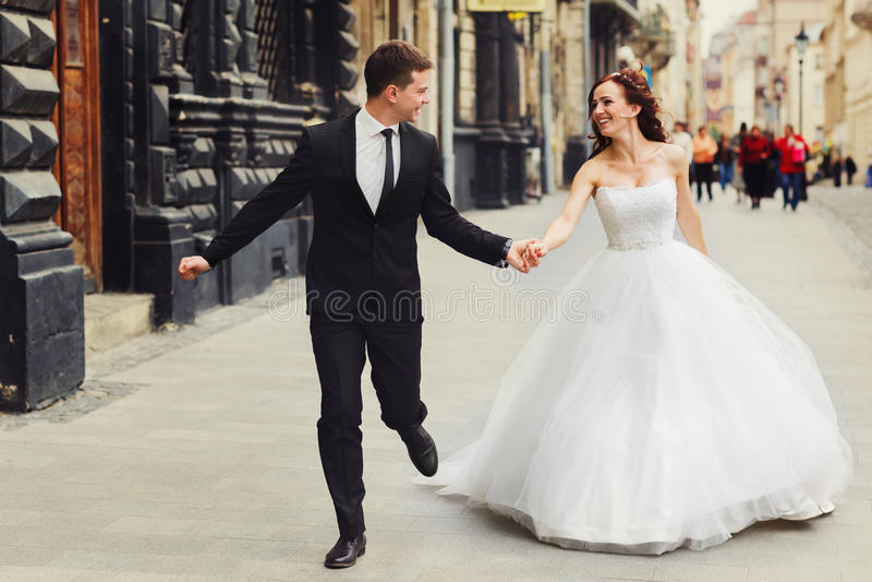 O noivo guarda a mão do ` s da noiva firmemente quando correrem ao longo do buildi velho imagem de stock