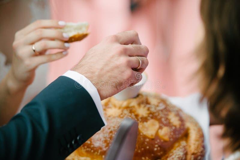 O noivo interrompe uma parte do naco do casamento fotos de stock