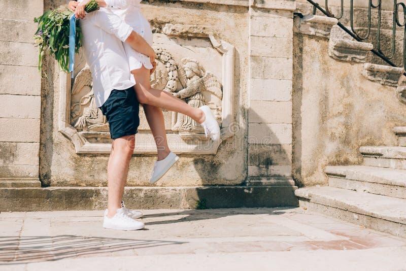 O noivo levantou a noiva em seus braços Close-up dos pés r foto de stock