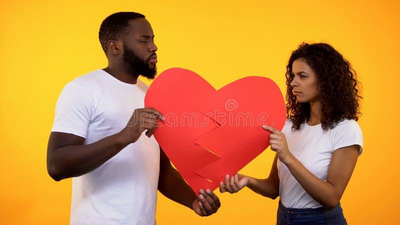 O noivo ofendido e a amiga que guardam as peças de papel do coração, relações opõem imagem de stock royalty free
