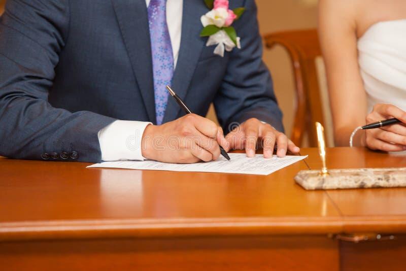 O noivo põe uma lista no original foto de stock