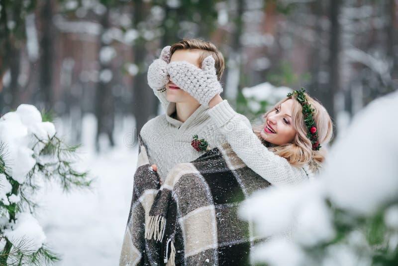 O noivo que bonito da coberta da menina o ` s eyes por ela fez malha mittes Casamento do inverno artwork fotos de stock royalty free