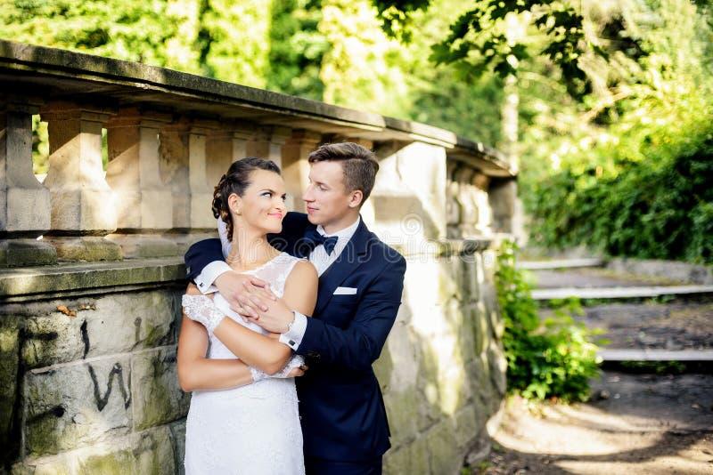 O noivo que está atrás da noiva e abraça-a fotografia de stock