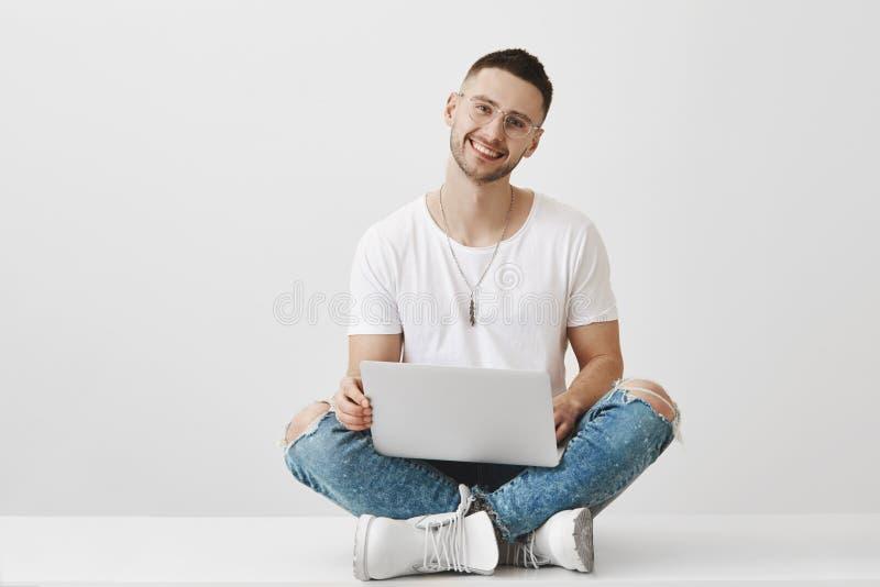 O noivo quer mostrar a seus pares algo no portátil Retrato do estudante farpado novo bonito em à moda foto de stock